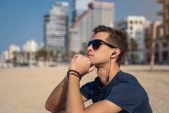 海滩听的音乐的年轻人与耳机 作为背景的城市地平线 库存照片