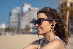 海滩听的音乐的年轻女人与耳机 作为背景的城市地平线 免版税库存照片