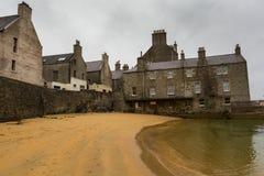 海滩和沿海岸区老石房子在Lerwick 库存图片
