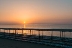 海滩在与太阳懒人的早晨 免版税库存照片
