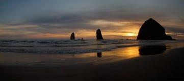 海滩在岩石日落的大炮干草堆 免版税库存照片