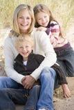 海滩坐二个年轻人的儿童母亲 库存照片