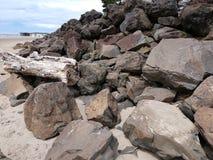 海滩堆冰砾和漂流木头与海滩沙子在前景在俄勒冈海岸在远的背景中是码头 库存照片