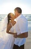 海滩夫妇亲吻的结婚的日落婚礼 免版税图库摄影