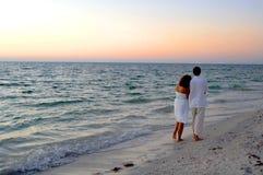 海滩夫妇日落走 库存图片