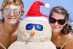 海滩夫妇纵向沙子雪人 免版税库存照片