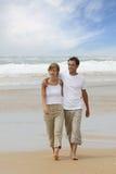 海滩夫妇走的年轻人 免版税库存图片