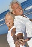 海滩夫妇递愉快的藏品前辈 免版税库存照片