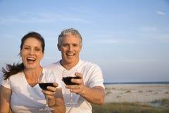 海滩夫妇饮用的酒 免版税库存图片