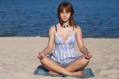 海滩女孩实践瑜伽年轻人 免版税库存图片