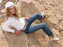 海滩女孩放置岩石 免版税库存图片