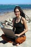 海滩女孩膝上型计算机 图库摄影