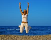 海滩女孩跳微笑 免版税库存照片