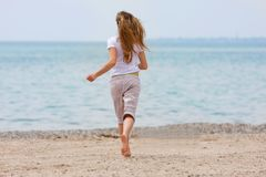 海滩女孩运行的年轻人 免版税库存照片