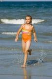 海滩女孩运行的年轻人 图库摄影