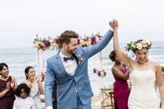 海滩婚礼仪式的快乐的新婚佳偶 免版税图库摄影
