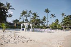 海滩婚礼地点安排在海边、曲拱、法坛有最小的花装饰的,棕榈树和椰子背景 图库摄影