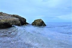 海滩岩石是发现小热带鱼的巨大地方在海洋表面下 免版税库存照片