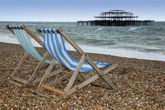 海滩布赖顿西方deckchairs的码头 库存图片