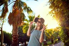 海滩帽子的年轻美女走在热带棕榈树下的在好日子在博德鲁姆,土耳其 假期户外海景 库存图片