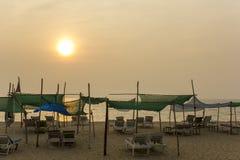 海滩床在一个沙滩以海为背景和太阳的机盖下在灰色天空 库存图片