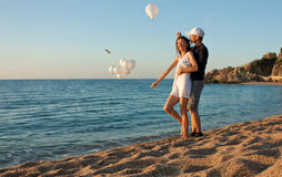 海滩愉快夫妇的乐趣有晴朗的年轻人 免版税库存照片