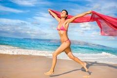 海滩愉快的布裙妇女 库存图片