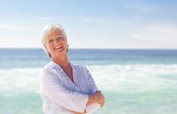 海滩愉快的退休的妇女 免版税库存照片