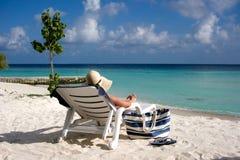 海滩懒人坐的星期日妇女 免版税库存图片