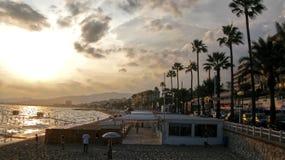 海滩戛纳,法国海滨的著名城市在与人游泳在夏天的-陆间海,法国的日落期间, 免版税库存照片
