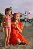 海滩接近坐女儿的母亲 免版税库存照片