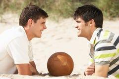 海滩放松二个年轻人的橄榄球人 库存照片