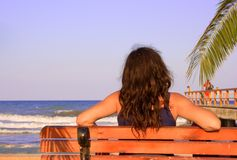海滩放松长凳的女性 免版税库存图片