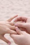 海滩新娘新郎放置环形婚礼 免版税库存图片