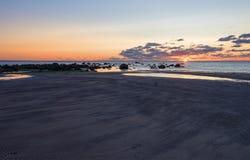 海滩日落是与波浪辗压的金黄天空 库存图片