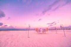 海滩晚餐设定 日落天空和椅子和桌浪漫夫妇背景的 免版税库存照片