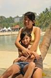 海滩有乐趣的女孩年轻人 图库摄影