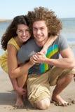 海滩有夫妇的乐趣年轻人 免版税库存图片