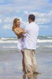海滩有夫妇的乐趣浪漫年轻人 免版税图库摄影