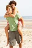 海滩有夫妇的乐趣肩扛年轻人 免版税库存照片