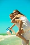 海滩有夫妇的乐趣年轻人 免版税库存照片