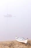 海滩有雾的皮船 库存照片