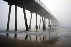 海滩有雾的hermosa码头日落 库存图片