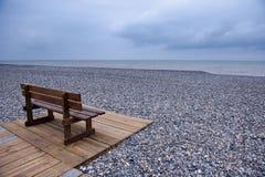 海滩木长凳的小卵石 库存图片