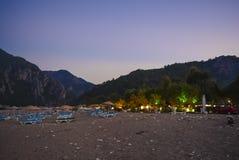 海滩棕榈在黄昏的海山Sunbeds 库存图片