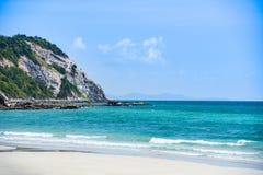 海滩沙子热带海夏天/海岛美丽的海滩清楚的水和喜怒无常的天空蔚蓝与小山岩石 库存照片