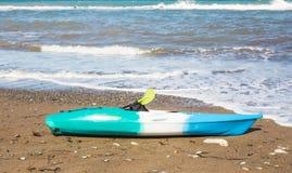 海滩活动,水上运动和划皮船的概念 在海滩的一艘明亮的蓝色皮船 库存照片