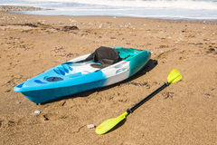 海滩活动,水上运动和划皮船的概念 在海滩的一艘明亮的蓝色皮船 图库摄影
