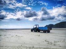 海滩清洁和拖拉机用于去除上面海滩残骸和黑暗的多云天空 库存图片