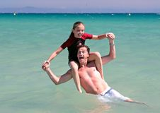 海滩演奏海运年轻人的女儿父亲 免版税库存图片